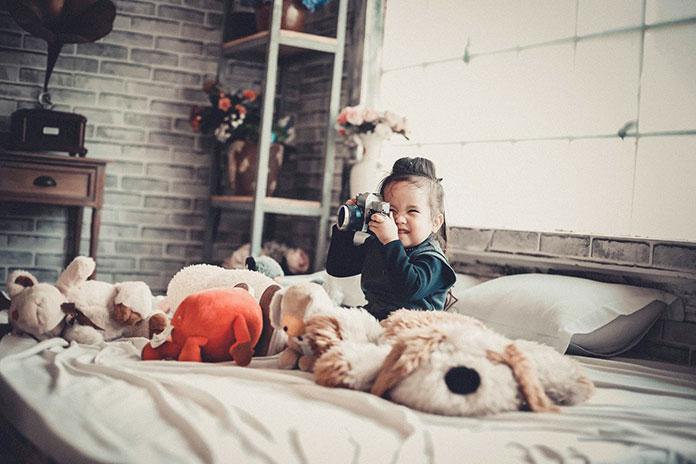 Dziecko trzymające aparat na tle szarej fototapety imitującej cegłę